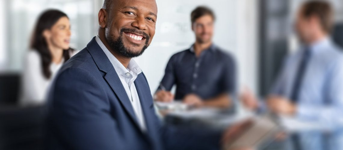 Mature black businessman with colleagues sitting in a modern board room. Proud smiling business man sitting during a meeting and looking at camera. Portrait of happy successful executive with team working in background.